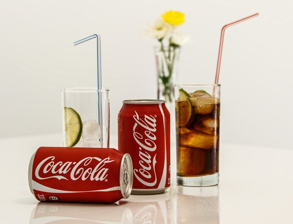 Two cans of Coca-Cola on a table next to filled glasses