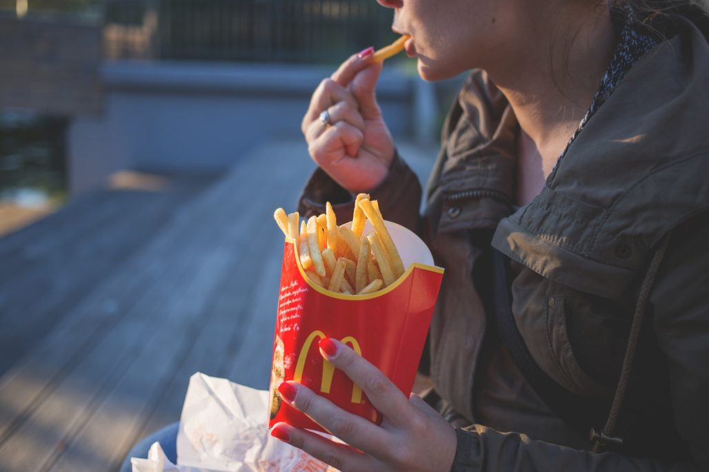 Woman eating Mcdonald's brand fries